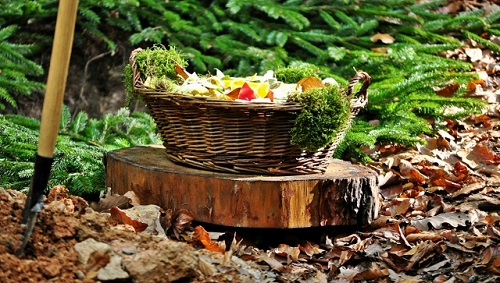 Das Bild zeigt einen Korb mit Blütenblättern und die Grabschaufel